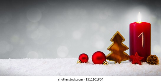 First Advent.Christmas background with Advent candle and red decoration.