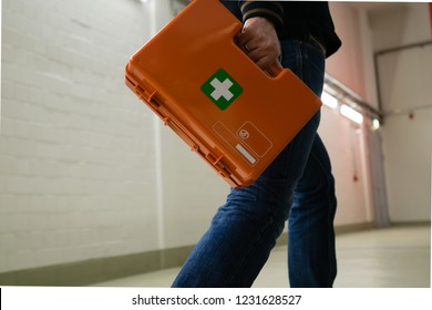 First aid after an accident at work. First responder with first aid kit, Germany.