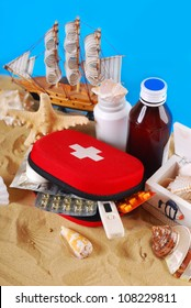 first aid box with medicines and thermometer  on the beach as healthy summer holiday concept