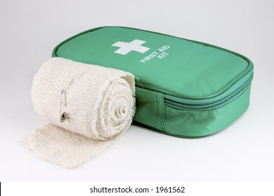 A first aid kit on white with bandage roll.