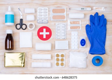 First aid kit on white, wooden background, top view
