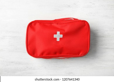 First aid kit on wooden background, top view. Health care