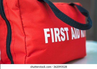First Aid Kit A red first aid kit bag with a black zip and handle, in closeup.