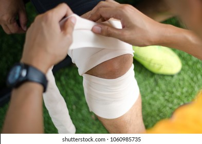First aid at knee trauma. First aid by gauze fabric.Injury from football matches