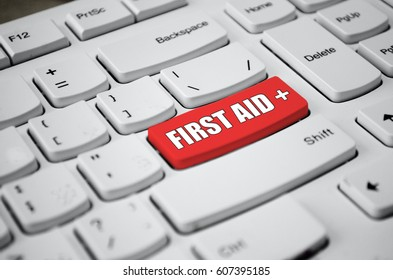 First aid text and cross symbol on red button of white keyboard.