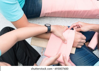 At First Aid Training Classroom, Students are trying to splint the arm of a patient's broken arm incident with cardboard and elastic bandage.