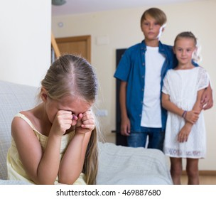 First amorousness: sad spanish girl and couple of kids apart indoors