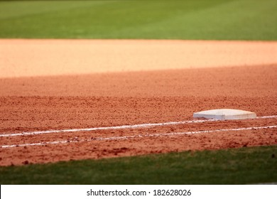 First base is featured in empty baseball field, showing infield dirt and outfield grass.