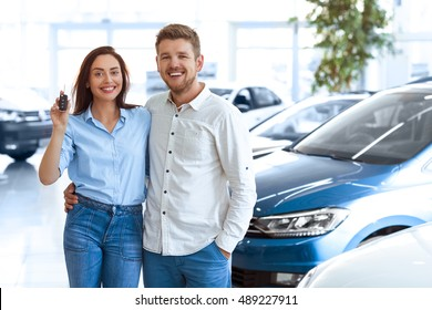 First big buy together. Portrait of a happy young couple hugging in a car salon showing car keys to a newly bought vehicle copyspace on the side