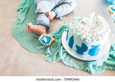 First Birhtday Cake baby male, smash cake, background shooting, green and blue with flags and baloons. Small feet baby jeans , 1st muffin blue