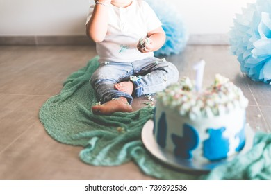 First Birhtday Cake baby male, smash cake, background shooting, green and blue with flags and baloons. Small feet baby jeans