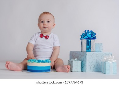 First birthday of the baby. Child eating cake with your hands. The child sits on the floor. Baby. Gifts for the child's birthday.