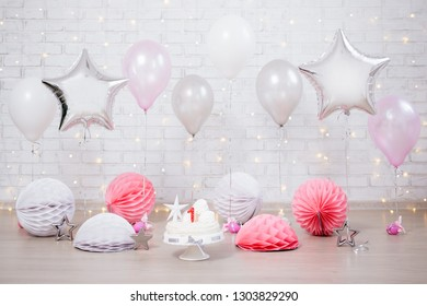 first birthday background - decorated room with cake and balloons over white brick wall