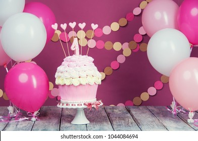 First birthday cake with a unit on a pink background with balls and paper garland.