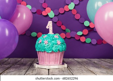 First birthday cake with a unit on a purple background with balls and paper garland