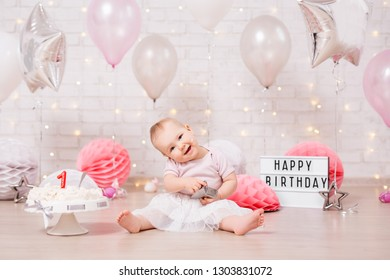 first birthday concept - funny dirty girl and smashed birthday cake over brick wall with lights and balloons