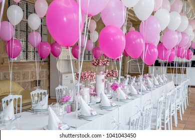 First birthday party of a baby concept made of white and pink colors balloons and candles