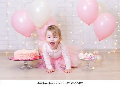first birthday party and happiness concept - happy little girl with cake and sweets over brick wall background with lights and colorful balloons