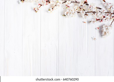 First blossom.Spring white flowers on vintage wooden background.Space for your text.