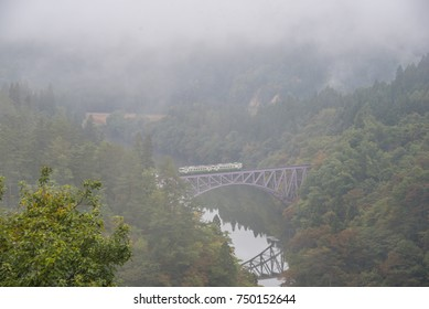 First bridge and Tadami river in beautiful autumn season on foggy day with train crossing the bridge in Japan