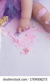 first cake. pink cake. the child takes the cake with his hand. hand in pastry cream. children's holiday