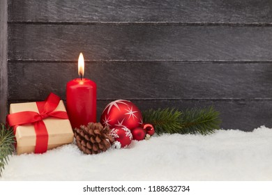 First christmas advent with red candle and decoration on wooden background