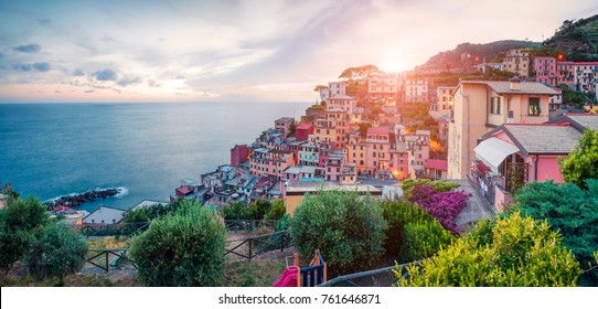 First city of the Cique Terre sequence of hill cities - Riomaggiore. Colorful spring sunset in  Liguria, Italy, Europe. Great evening seascape of Mediterranean sea. Traveling concept background.