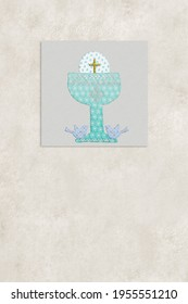 First communion invitations cards backgrounds. Chalice, host and doves on a piece of cloth on paper background with copy space for text, vertical image.