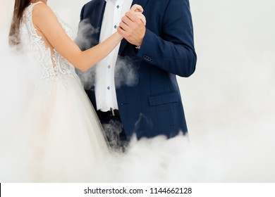 First dance at the wedding. Pair dancing in the fog, holding hands. Father and daughter dance
