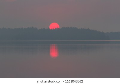 First dawn light from a tranquil, hazy summer sunrise over the islands of Stockholm archipelago, Sweden