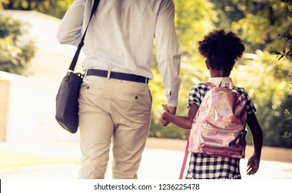 First day of school. African American father and his daughter walking trough park. From back. Close up.