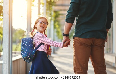 first day at school. father leads a little child school girl in first grade