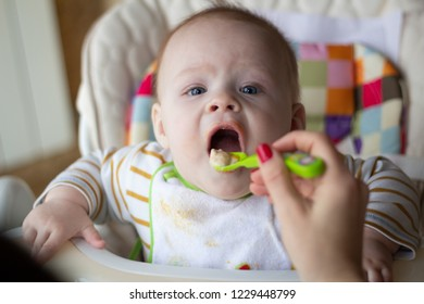 The first feeding of the baby from the spoon. Mom feeds baby homogenized chopped food with a spoon. child care