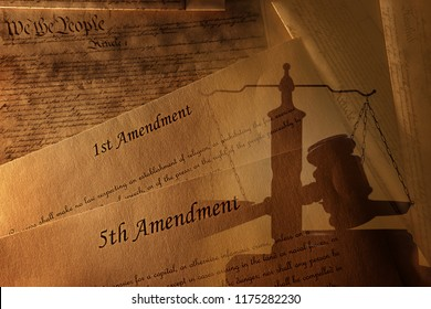 The First and Fifth Amendments and pages of the US Constitution with legal gavel and scales of justice