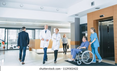 First Floor of the Busy Hospital, Doctors, Nurses and Personnel Busy Working, Assistant Moves Elderly Man in the Wheelchair. New Modern Medical Hospital with Professional Staff.