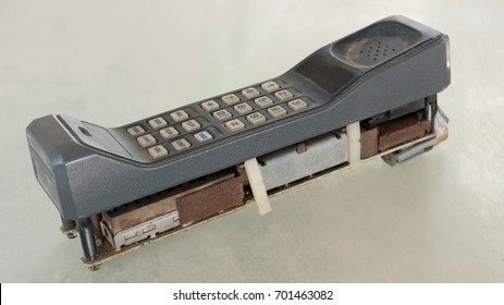 First generation style of cellular mobile phone with 1G or 2G on old table with vintage tone style. Big vintage mobile phone.