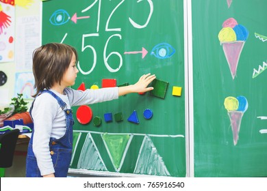 First grade boy at school, showing numbers and calculating in front of the blackboard