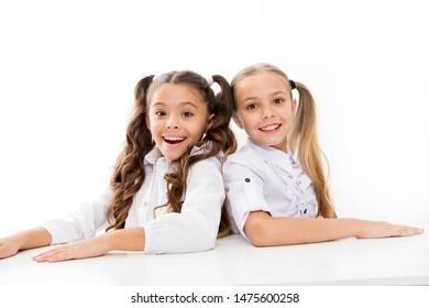 First grade. Happy childhood. Adorable schoolgirls. Back to school. Education concept. Beautiful girls best friends. Formal style. Schoolgirls sit desk white background. Schoolgirls emotional friends.