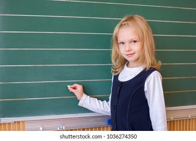 First grade pupil a girl writing on green blackboard at school lesson