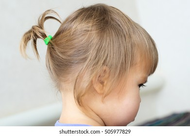 first hair style: tiny ponytail, profile of baby girl child