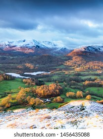 The first hint of winter up on Loughrigg Fell looking across over Elterwater and to the fells beyond from a November hike in the English Lake District.