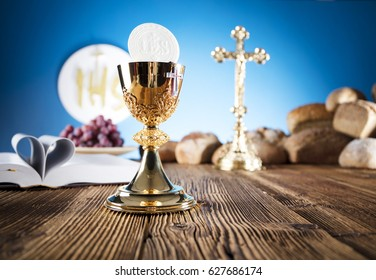 First Holy communion. Catholic theme. Crucifix, chalice, bible, bread on rustic wooden table and blue background.