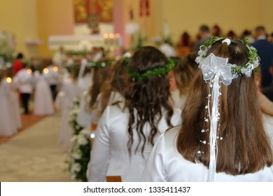 First Holy Communion event in catholic church, girls dressed in white dressed, with wreath on heads on their back, in soft focus altar, kids going to take first communion, decoration on walls