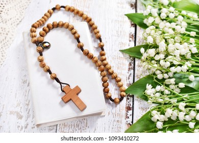 First Holy Communion still life with wooden rosary lying on prayer book and lily of the valley flower`s border-top view