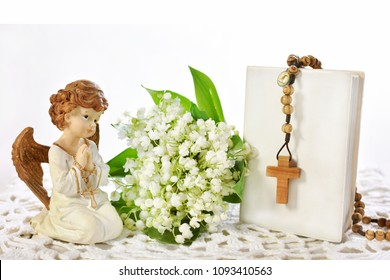 First Holy Communion still life with angel figurine,wooden rosary hanging on prayer book and bunch of lily of the valley flowers isolated on white with cope space for text