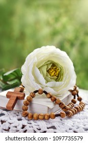First Holy Communion still life with wooden rosary lying on prayer book and white flower