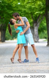 First kiss - Young couple of lovers in love passionately kissing standing on path in summer park. Full body portrait of Caucasian male and Asian female in blue sundress loving and hugging each other.
