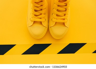 First in line young man queueing, conceptual overhead top view image of yellow sneakers waiting in line