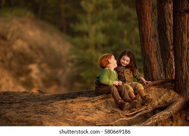 First love. Cute red-haired boy and beautiful little girl are sitting on the tree roots in the forest and talking. Image with selective focus and toning.