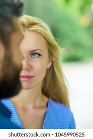 First meet of strangers, girl with calm face looks at bearded man. Blind date concept. Blind date, start of relations and dating. Couple meet on summer day, nature background, defocused.